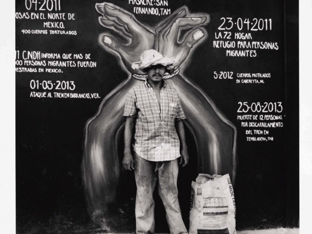 A man in frayed clothing stands in front of a mural marking a timeline of violent acts against immigrants. The mural's dates surround a large pair of hands, handcuffed together with rope.