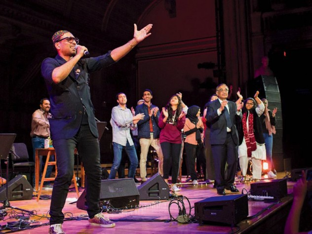 Singer Ali Sethi gestures toward the audience at Sanders Theatre, while students dance on stage behind him.