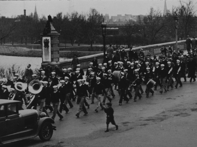 Band members wearing sailor hats march across a bridge to play at a football game