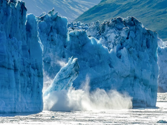 A photograph of a glacier breaking apart in Alaska, with large chunks of ice falling into the ocean.