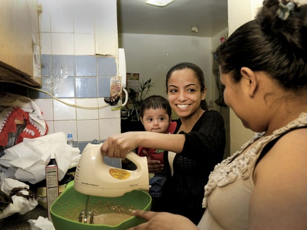 Katty Morocho (center), a social worker for Little Sisters, teaches client Zenaida Vega to bake a cake while Vega's nephew, Miguel, looks on. Vega hopes to find work at a bakery.