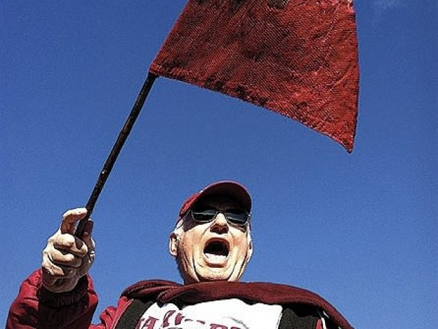 """Bill Markus '60 waving the Little Red Flag at Yale Bowl (see <a href=""""http://harvardmagazine.com/2003/09/superfan.html"""">""""Superfan""""</a>). Crimson loyalists have taken the flag to 124 Yale games since 1884; on Markus's watch, Harvard is now 12-1."""