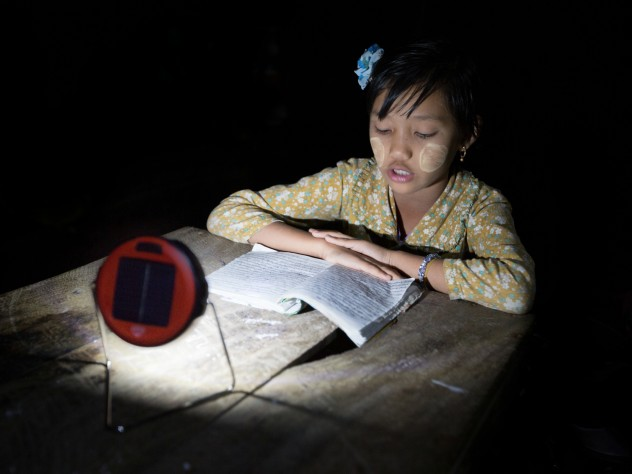 Proximity Designs now sells d.light solar lights—typically, on a multimonth installment plan. The basic light, shown here, has the most basic of uses: enabling reading, or homework, at night, in lieu of candles, which are expensive, a fire hazard in bamboo houses, and unsuitable for use under mosquito netting. (The white paste on the girl's cheeks is <i>thanaka,</i> a cosmetic paste made from ground bark, which many women and girls in Myanmar apply to guard against sunburn and to protect the skin.)