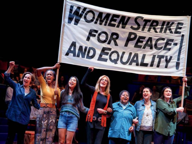 """Scene from """"Gloria, A Life,"""" showing women marching in solidarity with protest sign"""