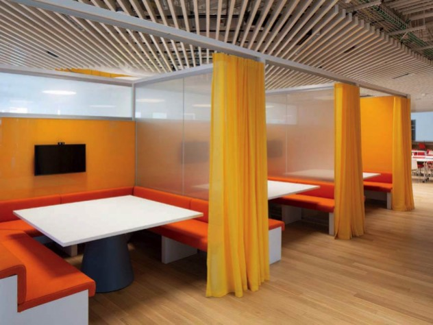 A centrally located 3,100-square-foot library has study carrels with orange benches, white desktops, and yellow privacy curtains.