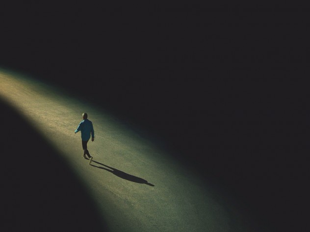 Drawing of a distant solitary figure walking alone toward the horizon along a narrowing path of light edged on both sides by darkness