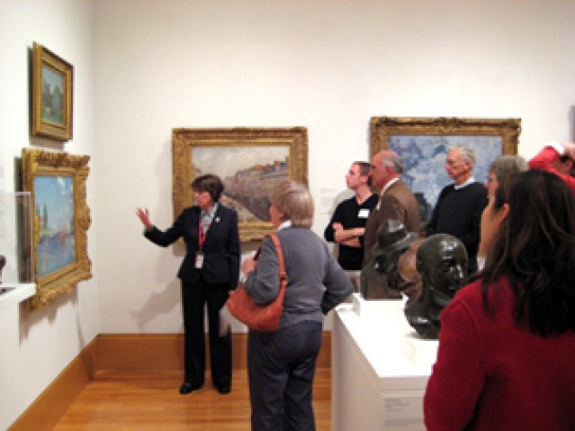 Docent Susan Glassman describes a painting to a group of guests
