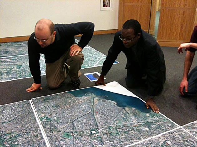 At the Center for Geographic Analysis office, the Harvard-MIT Data Center's Eric Alderman examines a map of Port-au-Prince with Jean-Lucien Ligonde, a businessman in the Boston Haitian community, in preparation for sending the map to Haiti to be used in relief work.