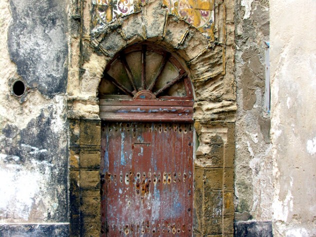Note the intact Roman keystone and distinctively Portuguese spoke-wheel woodwork in this weathered door in Essaouira, Morocco (2006).