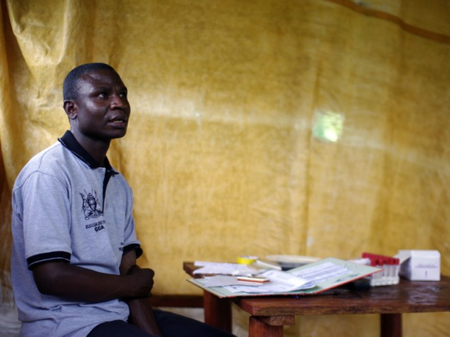 Physician Joshua Mukhama in the space where he conducts counseling: a gazebo with a sheet hung to separate the counseling area from the waiting area