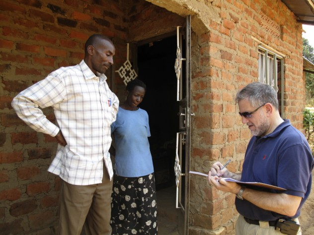 University Provost Steven Hyman, who visited Uganda in 2009 to learn about SHIP and other projects in Mbarara, signs the guest book at Nshemereirwe's house as Musinguzi looks on.