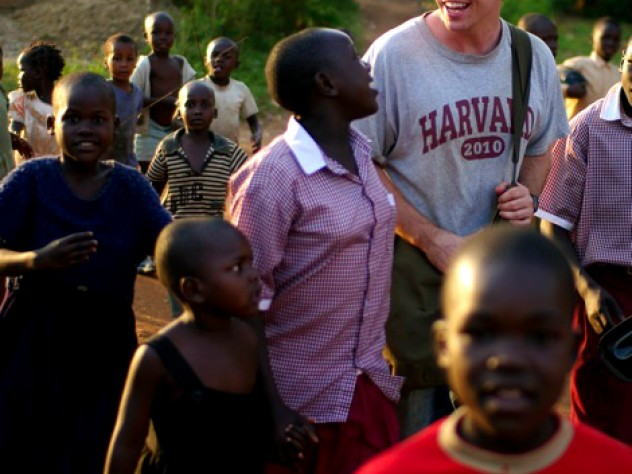 Christopher Higgins '10 walks through Busia, Uganda, in July with residents of the New Hope orphanage (wearing the crimson-and-white New Hope school uniform) and children from the community.