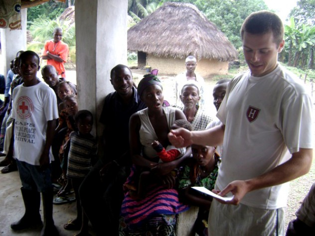 Using notes to bolster his command of Mende, the local language, Sam Slaughter '09 introduces himself and the GMin team to villagers.
