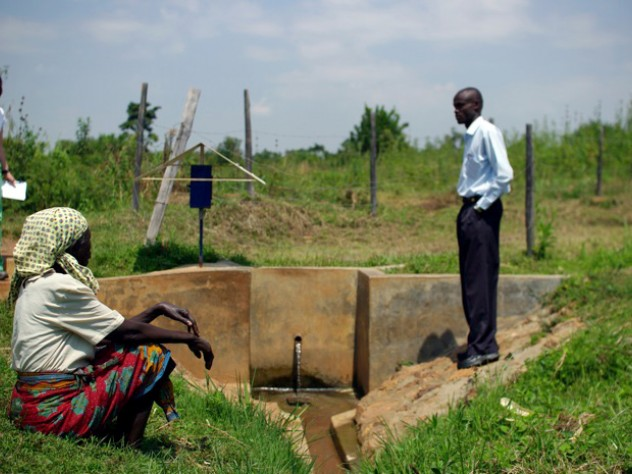 At a water collection site near Busia, Kenya, Leonard Bukeke, rural water project coordinator for IPA, shows the author around and introduces her to Seline Luyemba (foreground), the local resident who is responsible for making sure the dispenser gets refilled when it's near empty.