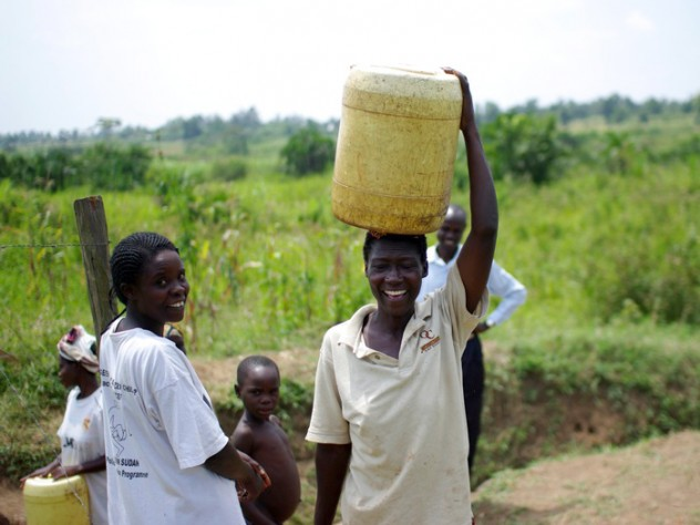 Loice Pamba (right) heads home with her (purified) water, while Everlyne Narocho—the resident responsible for making sure the dispenser stays filled at this site—looks on.