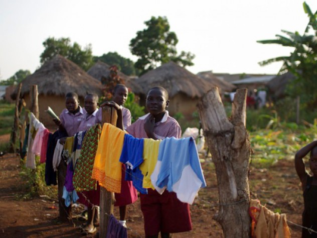 On the orphanage grounds, children hang laundry to dry.