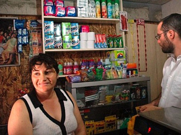 "Marta Herrera (pictured here with Gonzalo Arteaga) has set up a small convenience store in the front room of her house at the ELEMENTAL development in Lo Espejo. Herrera, who lives here with her husband and two children, says she was unemployed before. ""I prefer this,"" she says. ""My life is so happy now."""