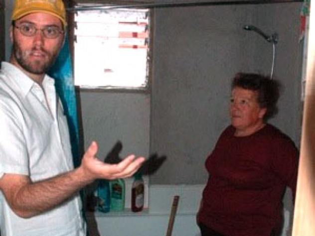 Ortega (right) talks with ELEMENTAL project manager Gonzalo Arteaga in the bathroom of her home. Despite the unfinished walls, residents are pleased that the bathroom in each unit has a bathtub and a window that opens.