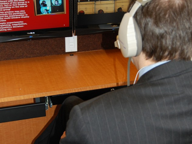 Each cubicle has two monitors that allow study participants to see the other participants (on the right-hand screen) alongside information or a stimulus presented by the experiment leader. Participants can communicate with one another through their headphones.