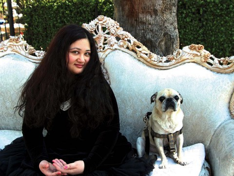 Author Gabrielle Zevin seated on a sofa in Los Angeles with her dog Nico
