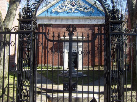 The arch of the delicate Class of 1870 Gate acts like a raised eyebrow, perfectly framing a view of Holden Chapel's ornate blue gable. The gate has been locked for decades, preventing pedestrians along Massachusetts Avenue from entering the chapel's intimate courtyard.