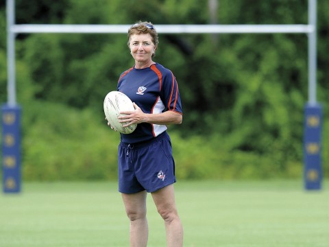Holding a rugby ball, Sue Parker stands before rugby goalposts. She is Harvard's first varsity coach in the sport.