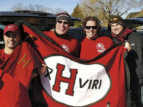 Members of the undefeated 2001 Crimson football team show flags at a 2011 tailgate in New Haven. Jared Lewis '02, far left, holds the ancient Little Red Flag, which has been to many Harvard-Yale football games. He designed the new flag, and Kelly Goff made it. It is brandished, from left, by Justin Stark '02, Jason Hove '02, and Samuel Taylor '02.