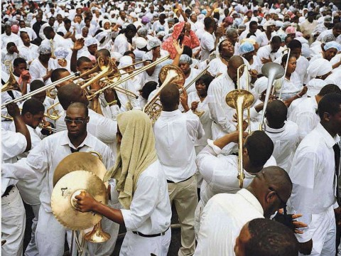 A street crowd of black men and women, all dressed in white, either playing or responding to the playing of dozens of trombones