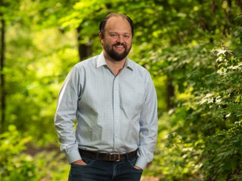Ross Douthat standing in a wooded park